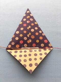 折り紙を開いてセロテープでひもを固定する