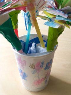 花瓶に見立てたコップに、キッチンペーパーと青い折り紙を破いて水を作る